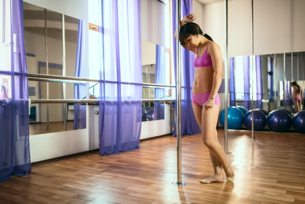 Joven morena de pie cerca de pilón en estudio de baile y pensando