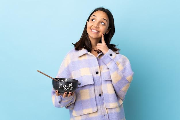 Joven morena de raza mixta mujer sosteniendo un cuenco lleno de fideos sobre la pared azul pensando una idea mientras mira hacia arriba