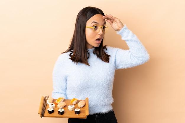 Joven morena de raza mixta mujer sosteniendo sushi aislado con expresión de sorpresa mientras mira hacia el lado