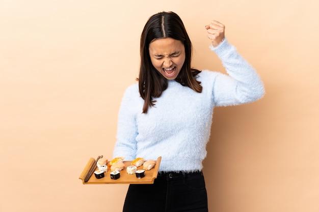 Joven morena de raza mixta mujer sosteniendo sushi sobre aislado celebrando una victoria