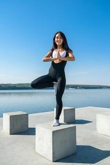 Joven morena en ropa deportiva haciendo estiramientos de piernas después del entrenamiento en el lago cerca del día. estilo de vida saludable