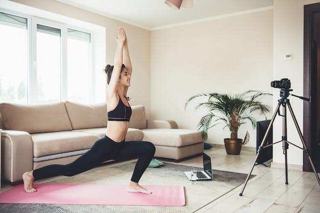 Joven morena en ropa deportiva haciendo fitness frente a cámara en una alfombra rosa