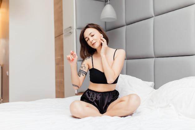 Joven morena en ropa interior sexy escuchando música con auriculares en la cama