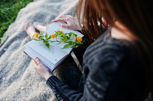 Joven morena sentada en tela escocesa y leer el libro.