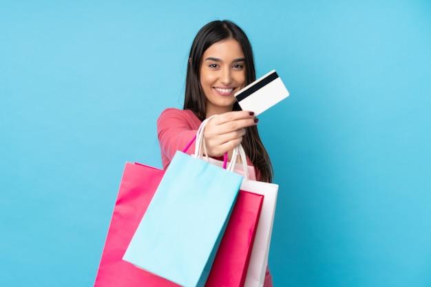 Joven morena sobre azul sosteniendo bolsas de compra y una tarjeta de crédito
