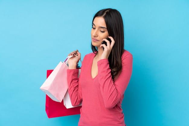 Joven morena sobre azul sosteniendo bolsas de compras y llamando a un amigo con su teléfono celular