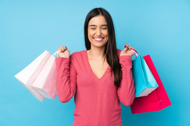Joven morena sobre azul sosteniendo bolsas de compras y sonriendo