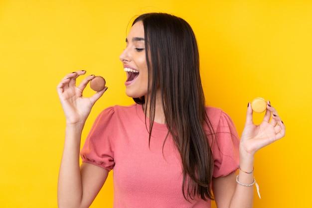 Joven morena sobre pared amarilla aislada sosteniendo coloridos macarons franceses y comiendo