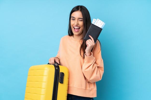 Joven morena sobre pared azul aislada en vacaciones con maleta y pasaporte
