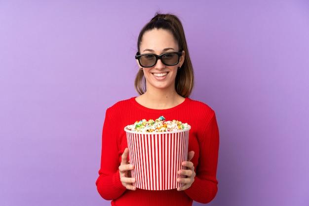 Joven morena sobre pared púrpura aislada con gafas 3d y sosteniendo un gran cubo de palomitas de maíz