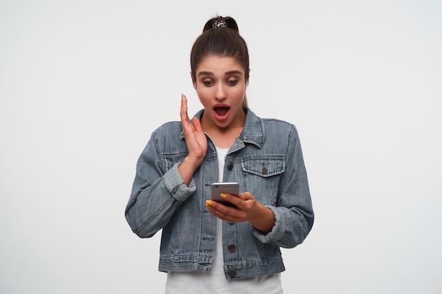 Joven morena sorprendida con la boca abierta en camiseta blanca y chaquetas de mezclilla, sostiene un teléfono inteligente y parece sorprendida, escuchando la nueva canción de su banda favorita.