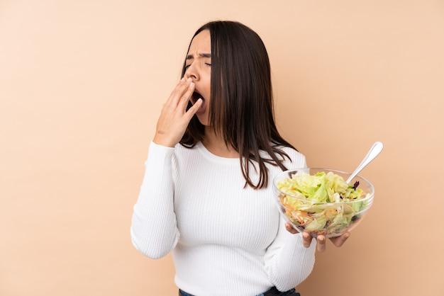 Joven morena sosteniendo una ensalada sobre bostezos aislados y cubriendo la boca abierta con la mano