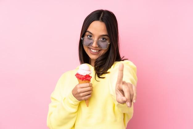 Joven morena sosteniendo un helado de cucurucho sobre rosa mostrando y levantando un dedo