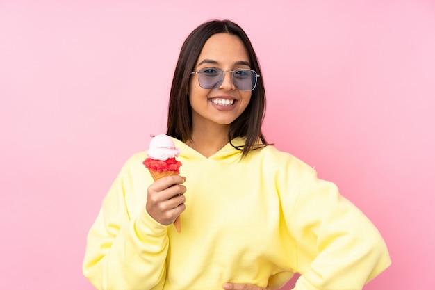 Joven morena sosteniendo un helado de cucurucho sobre rosa posando con los brazos en la cadera y sonriendo
