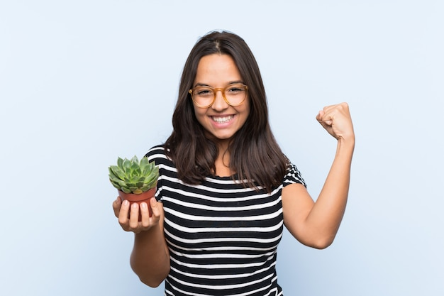 Joven morena sosteniendo una planta celebrando una victoria