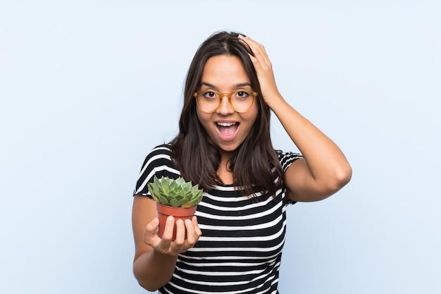 Joven morena sosteniendo una planta con sorpresa y expresión facial conmocionada