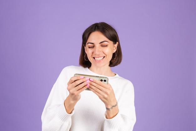 Joven morena en suéter casual blanco aislado en la pared púrpura