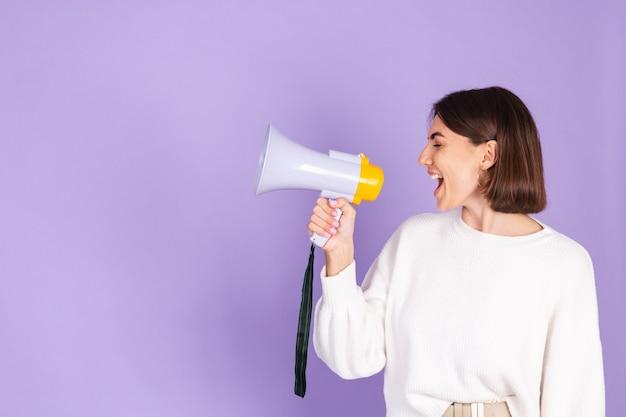 Joven morena en suéter casual blanco aislado en la pared púrpura Foto gratis