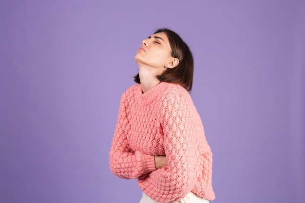 Joven morena en suéter rosa aislado en la pared púrpura