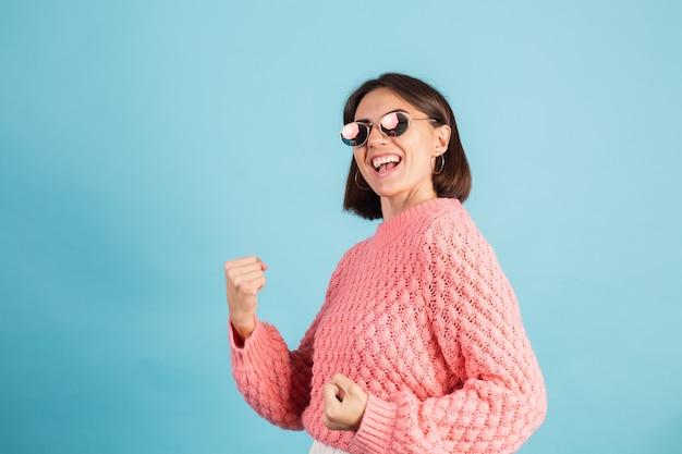 Joven morena en suéter rosa cálido aislado en la pared azul