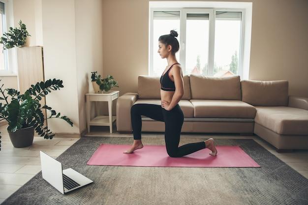 Joven morena vistiendo ropa deportiva está haciendo yoga en una alfombra rosa usando una computadora portátil