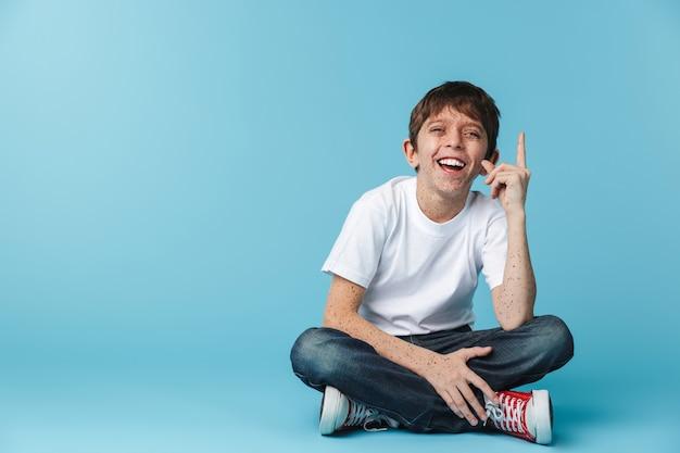De joven morenito con pecas vistiendo camiseta blanca casual mostrando el dedo hacia arriba mientras está sentado en el piso aislado sobre la pared azul