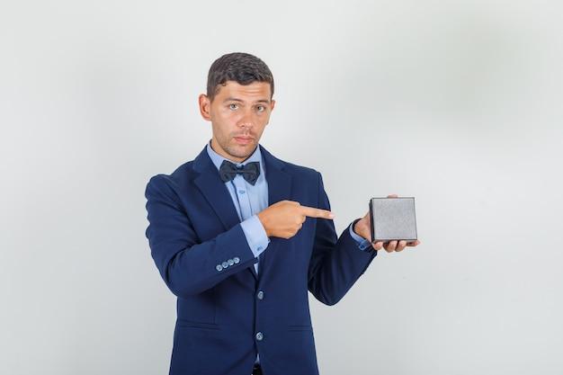 Joven mostrando caja de reloj con dedo en traje