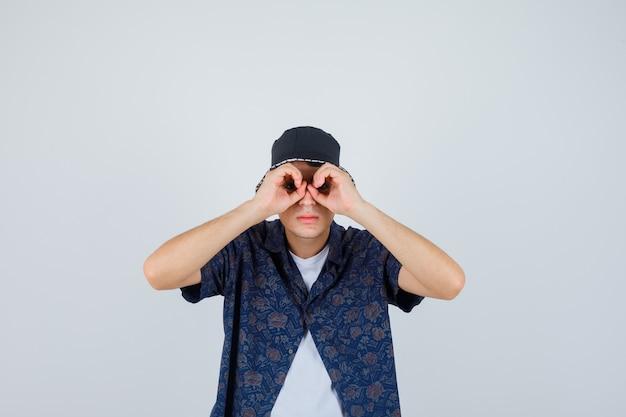 Joven mostrando gesto de binoculares en camiseta blanca, camisa floral, gorra y mirando serio.