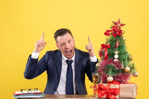 Joven mostrando la lengua apuntando con el dedo hacia arriba sentado en la mesa cerca del árbol de navidad y presenta en amarillo