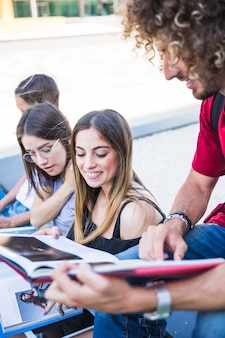 Joven mostrando libros de texto a las mujeres