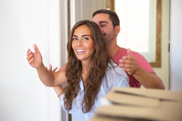 Joven mostrando nuevo apartamento a su novia feliz sorprendida