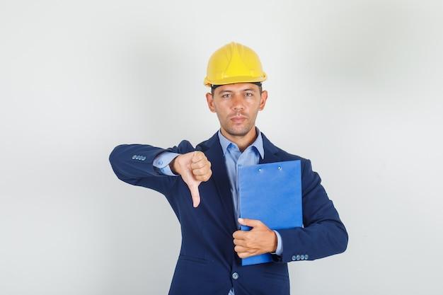 Joven mostrando el pulgar hacia abajo con el portapapeles en traje, casco de seguridad y mirando disgustado