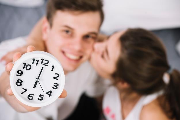 Joven mostrando reloj con 6 am