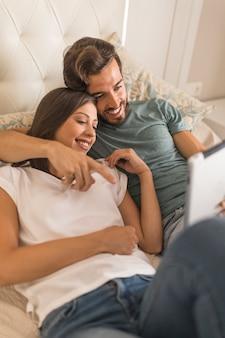 Joven mostrando tableta a su novia en la cama