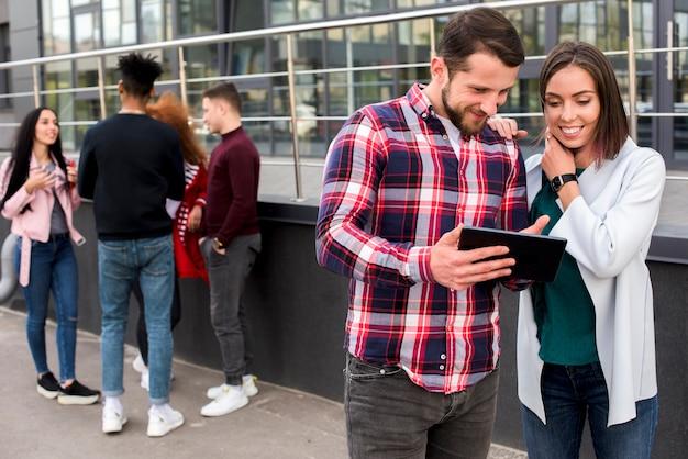 Joven mostrando tableta digital a su amigo de pie junto a la multitud