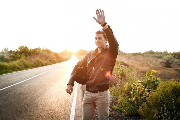 Joven motociclista guapo saludo, sosteniendo el casco, posando en el camino rural.