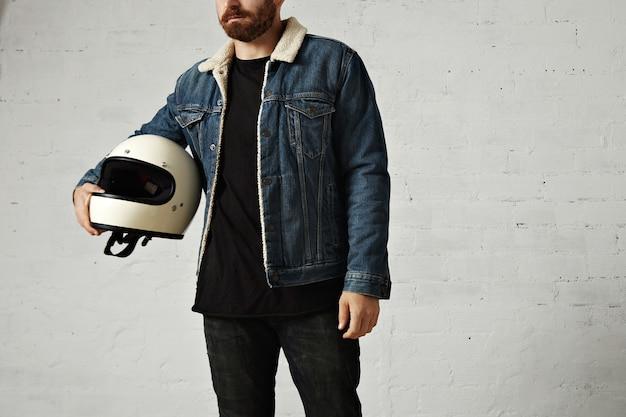 Un joven motorista irreconocible viste una chaqueta de mezclilla de piel de oveja y una camiseta henley negra en blanco, abraza su casco de motocicleta beige vintage, aislado en el centro de la pared de ladrillo blanco