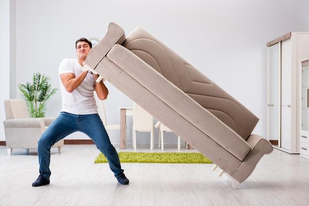 Joven moviendo muebles en casa   Foto Premium