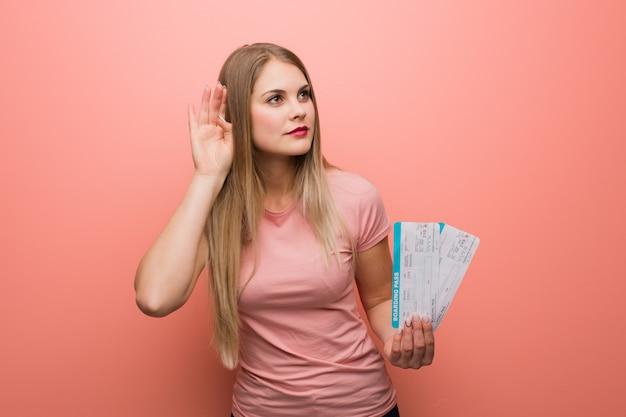 Joven muchacha rusa bonita intenta escuchar un chisme. ella está sosteniendo unos billetes de avión.