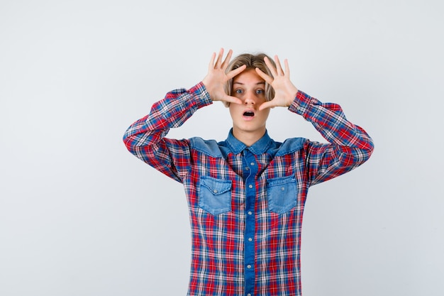 Joven muchacho adolescente en camisa de cuadros asomándose a través de los dedos y mirando preguntado