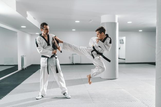 Joven muchacho caucásico en dobok pateando descalzo mientras el entrenador sostiene el objetivo de la patada. concepto de entrenamiento de taekwondo.