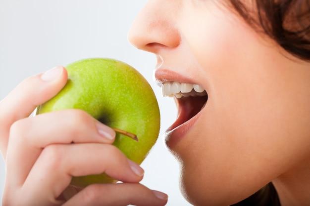 Joven muerde en una manzana fresca y saludable