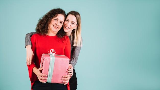 Joven mujer abrazando a madre con regalo