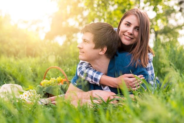 Joven mujer abrazando novio en reposo en la naturaleza
