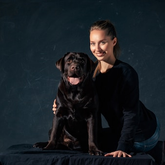 La joven mujer abrazando a un perro de raza mix