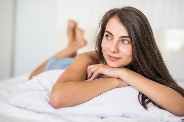 Joven mujer acostada al final de la cama debajo de la colcha y sonriendo, con la cabeza apoyada en la mano y la otra en el pelo.