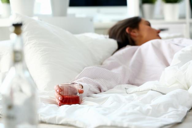 Joven mujer acostada en la cama borracho mortal