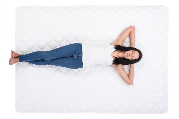 Joven mujer está acostada en la cama y el descanso.