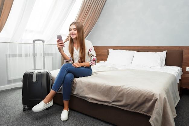 Joven mujer acostada en la cama de una habitación de hotel