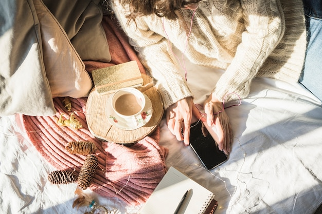 Joven mujer acostada en la cama con una taza de café y el uso de smartphone